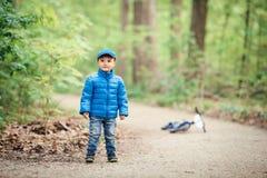 pojkelilla barnet i blått omslag, jeans och baseballmössan parkerar in lekplatsen utanför med cykeln på vårhöstdag Arkivfoto