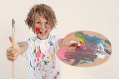 Pojkemålning med borsten och pallete Arkivfoton