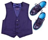 Pojkemörker - den blåa västen med flugan och moderna skor isoleras på vit Arkivbild