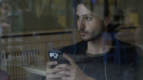 Pojkemaskinskrivningmeddelanden på hans smartphonesammanträde i ensamma väntande vänner för en bar som kommer stock video