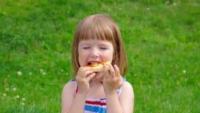pojkematställegräs har little pizza två för ängmiddagpicknick den små flickan har en matställe med pizza på ängen arkivfilmer