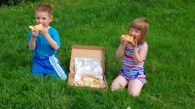 pojkematställegräs har little pizza två för ängmiddagpicknick pojken och den lilla flickan har en matställe med pizza på ängen lager videofilmer