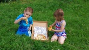 pojkematställegräs har little pizza två för ängmiddagpicknick pojken och den lilla flickan har en matställe med pizza på ängen arkivfilmer