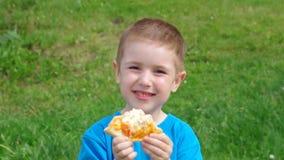pojkematställegräs har little pizza två för ängmiddagpicknick pojken och den lilla flickan har en matställe med pizza på ängen stock video