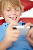 pojkemobiltelefon genom att använda barn Royaltyfri Fotografi