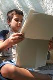 pojkemorgonnyheterna läser royaltyfri bild