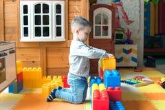 Pojken är 4 gamla år, de blonda lekarna på lekplatsen inomhus, bygganden en fästning från plast- kvarter arkivfoton