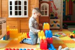Pojken är 4 gamla år, de blonda lekarna på lekplatsen inomhus, bygganden en fästning från plast- kvarter royaltyfria bilder