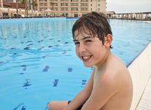 Pojken är har gyckel i simbassängen Royaltyfria Foton