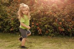 Pojken är på en gå pojkebarn med gulligt framsidaanseende på ett ben Arkivfoto