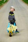 Pojken är på vägen med en bukett av blommor Arkivbilder