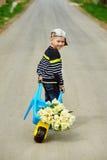 Pojken är på vägen med en bukett av blommor Royaltyfri Fotografi