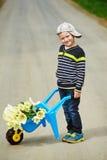Pojken är på vägen med en bukett av blommor Royaltyfri Foto