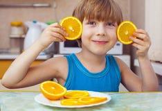 Pojken äter apelsinen Royaltyfri Foto
