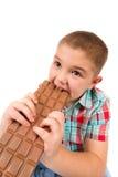 Pojken äter choklad royaltyfria foton