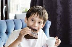 Pojken äter ett stort stycke av kakan Royaltyfria Foton