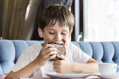 Pojken äter ett stort stycke av kakan Royaltyfri Foto