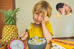 Pojken äter frukt men drömmar om hamburgaren Skadlig och sund mat för barn Barn som äter det sunda mellanmålet vegetarian arkivfoto