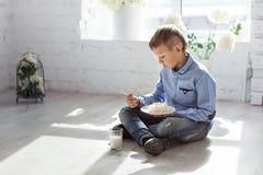Pojken äter kesosammanträde på golvet Arkivbild