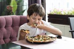 Pojken äter pizza Royaltyfri Foto