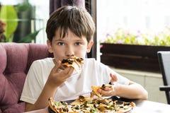 Pojken äter pizza Royaltyfri Bild