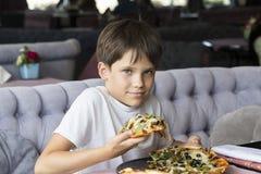 Pojken äter pizza Royaltyfria Bilder