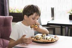 Pojken äter pizza Royaltyfria Foton