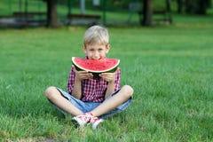 Pojken äter vattenmelon Arkivbild
