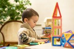 Pojken 2 år som bygger ett torn från en ljus och färgrik formgivare Intellektuella leksaker Arkivfoto
