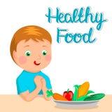 Pojken önskar att äta sund mat Sund livsstil På tabellen är en platta av grönsaker Royaltyfria Bilder
