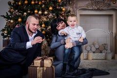 Pojken öppnar gåvan till föräldrar på jul, föräldrar kysser sonen på jul arkivfoton