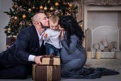 Pojken öppnar gåvan till föräldrar på jul, föräldrar kysser sonen på jul royaltyfri fotografi