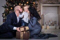 Pojken öppnar gåvan till föräldrar på jul, föräldrar kysser sonen på jul arkivfoto