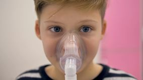 Pojken andas till och med en inhalator Maskering på hans framsida, närbild lager videofilmer