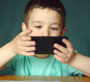 Pojken använder smartphonen royaltyfri fotografi