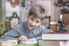 Pojken av 8 år lär huskurser royaltyfria foton