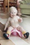 Pojken av 8 månader sitter på en kruka arkivbilder