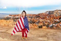 Pojken bär USA flaggan som firar 4th Juli Royaltyfri Foto