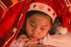 Pojken bar en julhatt under en filt, SAD och bara i fotografering för bildbyråer
