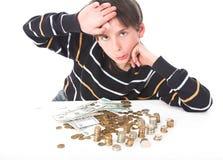 Pojken betraktar pengar royaltyfri foto