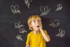 Pojken bitas av myggor på en mörk bakgrund På svart tavla med krita målade myggor royaltyfri bild