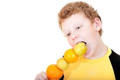 Pojken biter äpplesteknålarna Royaltyfri Fotografi