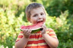 Pojken biter av ett stycke av vattenmelonen Royaltyfria Foton