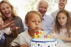 Pojken blåser ut stearinljus för födelsedagkakan på familjpartiet Fotografering för Bildbyråer