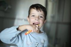 Pojken borstar hans tänder med lyckligt uttryck på framsidan fotografering för bildbyråer