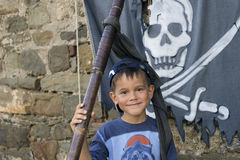Pojken bredvid piratkopieraflaggan Arkivbild