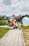 pojken bubbles helium som little motobike förföljer Arkivfoton