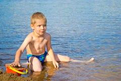 Pojken bygger en sand royaltyfri foto