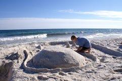Pojken bygger sandslotten royaltyfri bild