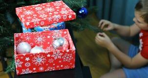 Pojken dekorerar julgranen med girlander och bollar för det nya året lager videofilmer